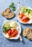 早餐或快餐两块板材-怂恿在蓝色背景的沙拉、三文鱼和鲕梨纯汁浓汤,顶视图 健康的食物 库存图片