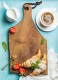 早餐或点心集合 新近地被烘烤的新月形面包用草莓、在盛奶油小壶的咖啡和牛奶在棕色木 库存照片