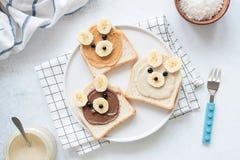 早餐敬酒用坚果黄油和香蕉与逗人喜爱的滑稽的动物面孔 孩子Food.Fun蝴蝶形状的薄煎饼用桃子 库存图片