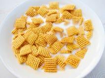 早餐方形玉米片用在碗的牛奶 库存照片