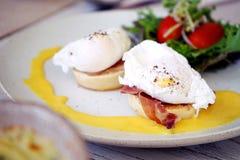 早餐是鸡蛋本尼迪克特,包括鸡蛋、英格兰式松饼、加拿大熏肉和蛋黄奶油酸辣酱调味汁供食用在白色安置的沙拉 免版税库存照片