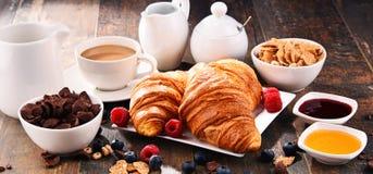 早餐服务用咖啡、新月形面包、谷物和果子 图库摄影