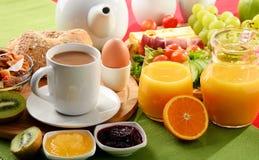 早餐服务用咖啡、橙汁、鸡蛋和果子 库存照片