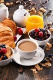 早餐服务用咖啡、汁液、新月形面包和果子 图库摄影