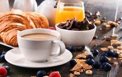 早餐服务用咖啡、汁液、新月形面包和果子 库存图片