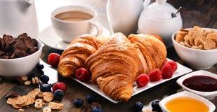 早餐服务用咖啡、汁液、新月形面包和果子 免版税库存照片