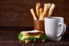 早餐桌用三明治、面包棒和无奶咖啡在土气木背景,特写镜头,选择聚焦 免版税库存图片
