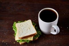 早餐桌用三明治和无奶咖啡在土气木背景,特写镜头,选择聚焦 库存照片