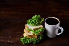 早餐桌用三明治和无奶咖啡在土气木背景,特写镜头,选择聚焦 免版税库存图片