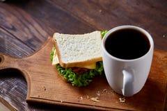 早餐桌用三明治和无奶咖啡在木切板在土气背景,特写镜头,选择聚焦 库存图片