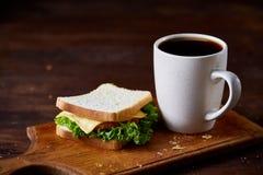 早餐桌用三明治和无奶咖啡在木切板在土气背景,特写镜头,选择聚焦 库存照片