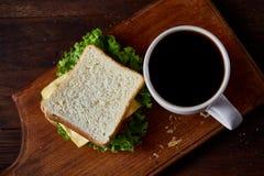 早餐桌用三明治和无奶咖啡在木切板在土气背景,特写镜头,选择聚焦 免版税库存图片