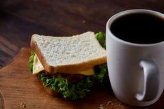 早餐桌用三明治和无奶咖啡在木切板在土气背景,特写镜头,选择聚焦 图库摄影