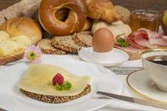 早餐桌用乳酪面包、咖啡、鸡蛋、火腿和果酱 库存图片