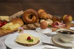 早餐桌用乳酪面包、咖啡、鸡蛋、火腿和果酱 免版税库存图片