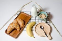 早餐桌用新月形面包和Muesli和香蕉和新鲜的牛奶 免版税图库摄影