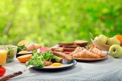 早餐桌用煎蛋、新月形面包、果子、沙拉和ju 库存图片