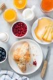 早餐桌,轻快早餐食物 新月形面包、乳酪、果酱、莓果、蜂蜜和鸡蛋 图库摄影