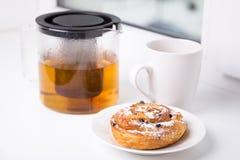 早餐概念-甜小圆面包用葡萄干和茶 库存图片