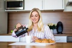 早餐概念-美丽的在现代成套工具的妇女倾吐的咖啡 库存照片