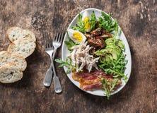早餐沙拉-煮沸的鸡,鲕梨,鸡蛋,芝麻菜, kumato蕃茄,在木棕色背景的烟肉 免版税库存图片