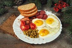 早餐油煎的鸡蛋、绿豆蕃茄、烟肉和面包 库存图片