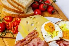 早餐煎蛋、面包、蕃茄、火腿和胡椒在木桌上 库存照片