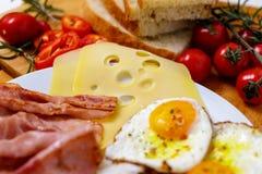早餐煎蛋、面包、蕃茄、火腿和胡椒在木桌上 免版税库存图片