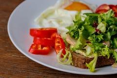 早餐煎蛋、面包、蕃茄、hummus、胡椒和rucola在木桌上 图库摄影