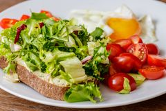 早餐煎蛋、面包、蕃茄、hummus、胡椒和rucola在木桌上 免版税库存图片