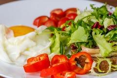 早餐煎蛋、面包、蕃茄、hummus、胡椒和rucola在木桌上 库存图片