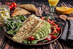 早餐煎蛋卷用鲕梨,蕃茄,无盐干酪乳酪,橙汁, samsa 健康的食物 免版税库存图片