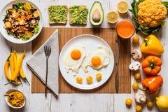 早餐煎蛋的,素食主义者鲕梨三明治,素食者沙拉,红萝卜新鲜汁和不同健康食物 库存照片
