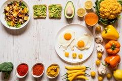 早餐煎蛋的,素食主义者鲕梨三明治,素食者沙拉,红萝卜新鲜汁和不同健康食物 免版税库存照片