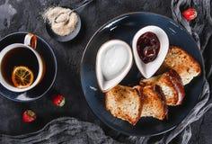 早餐用在板材的甜自创小圆面包在黑暗的背景,酸奶,草莓酱,一杯茶 面包店,酥皮点心,点心, 库存照片