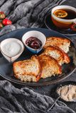 早餐用在板材的甜自创小圆面包在黑暗的背景,酸奶,草莓酱,一杯茶 面包店,酥皮点心,点心, 图库摄影