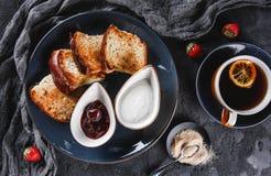 早餐用在板材的甜自创小圆面包在黑暗的背景,酸奶,草莓酱,一杯茶 面包店,酥皮点心,点心, 免版税库存图片