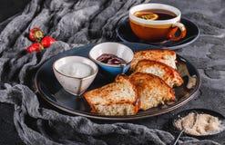 早餐用在板材的甜自创小圆面包在黑暗的背景,酸奶,草莓酱,一杯茶 面包店,酥皮点心,点心 库存图片