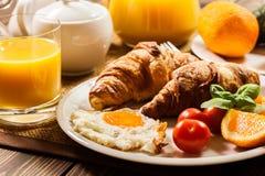早餐用新月形面包末端橙汁 免版税库存照片