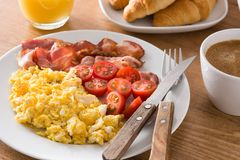 早餐用炒蛋、烟肉、蕃茄、咖啡、橙汁过去、新月形面包和玉米片 免版税图库摄影