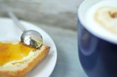 早餐用牛奶咖啡和蜂蜜面包 免版税图库摄影