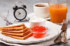 早餐稀薄的薄煎饼用在白色碗的红色鱼子酱 免版税库存照片