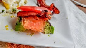 早餐膳食用鸡蛋和被堆积的鲕梨、冷的熏制鲑鱼熏鲑鱼、烟肉和蕃茄在白色陶瓷板材顶部 免版税库存照片