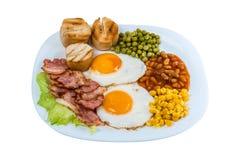 早餐荷包蛋豌豆、玉米五谷、豆和油煎的烟肉在一块白色板材 库存照片
