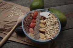 早餐莓果圆滑的人碗冠上了用莓, Chia,亚麻籽,椰子,坚果 库存图片