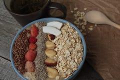 早餐莓果圆滑的人碗冠上了用莓, Chia,亚麻籽,椰子,坚果 免版税库存图片