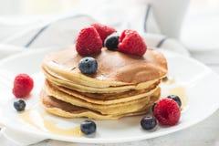 早餐莓果 薄煎饼 在一张木桌上的浪漫早餐 蓝色多云域草绿色早晨天空春天 舒适 免版税库存图片