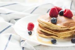 早餐莓果 薄煎饼 在一张木桌上的浪漫早餐 蓝色多云域草绿色早晨天空春天 舒适 免版税库存照片
