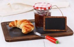 早餐菜单用新月形面包和果酱在白色木backgrou 库存图片