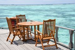 早餐设定了与木桌和椅子在海洋附近 免版税库存图片